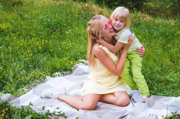 Мама и сын обнимаются на одеяле в парке. портрет крупным планом. женщина в розовых очках