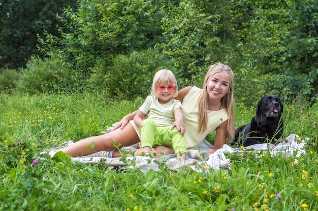 엄마와 아들은 강아지와 함께 공원에서 쉬고 있습니다. 핑크 선글라스에 소년입니다. 어머니의 날