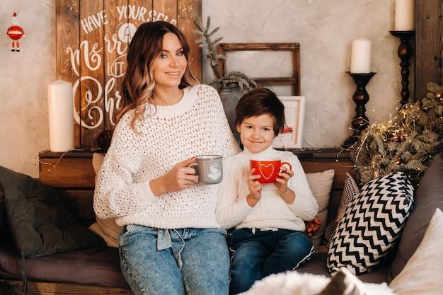 ママと息子は、贈り物とコーヒーを手に、自宅のソファに座っています。幸せな家族