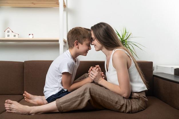 Мама и сын сидят на диване с закрытыми глазами и прислоненными лбами друг к другу
