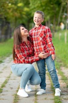公園の散歩でママと息子が幸せそうに笑っています。あらゆる目的のために。
