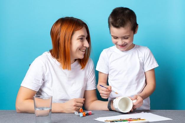 ママと息子は陽気に笑って、青い背景に明るいオレンジ色でふたを描いています。子供のための描画学習の概念