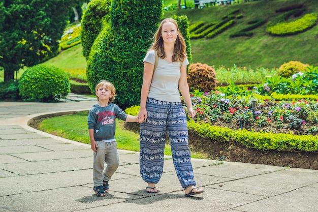 엄마와 아들은 열대 공원에서 걷고있다
