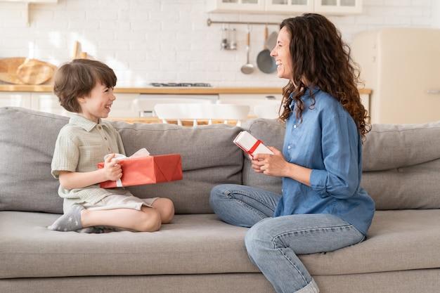 엄마와 아들이 함께 생일을 축하하고 행복한 엄마와 흥분한 아들이 소파에 앉아 웃고 있는 선물을 들고 있다