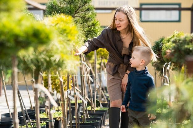 엄마와 아들은 정원 센터에서 식물을 선택합니다