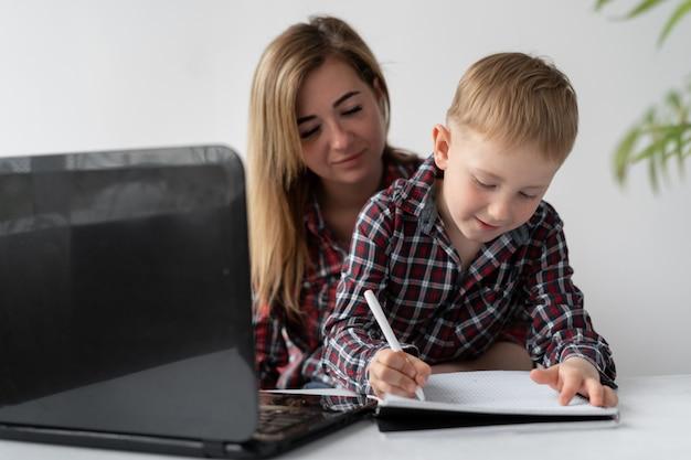 ママと息子は宿題をします。遠隔学習学生。女性は子供がレッスンのトピックを学ぶのを手伝います。少年は答えをノートに書きます。隔離されたオンライン教育。