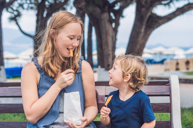 엄마와 아들이 공원에서 튀긴 고구마를 먹고