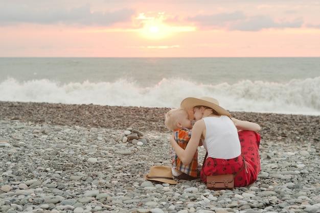 Мама и сын обнимаются на галечном пляже. время заката. вид сзади