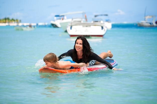 Мама и сын занимаются серфингом в океане на доске