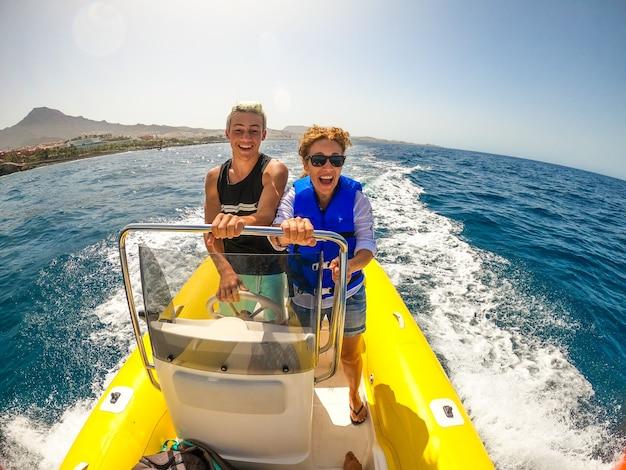 엄마와 아들은 보트를 타고 함께 즐기고 웃고 웃고 웃는 바다를 발견합니다 - 야외에서 작은 배와 함께 휴가와 휴가
