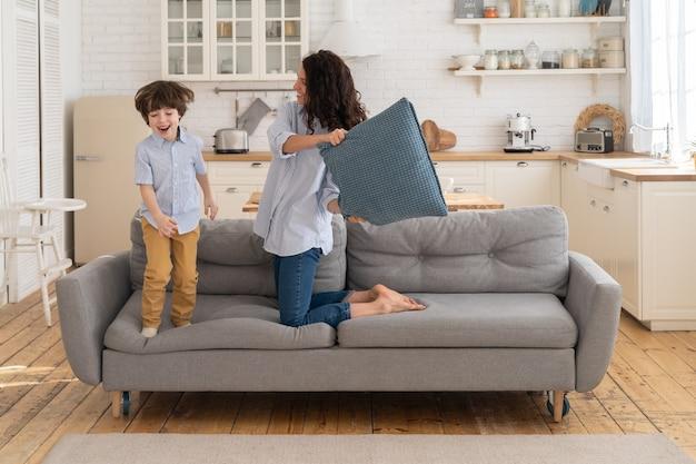 Мама и сын веселятся в гостиной, борются с подушками вместе семейный досуг и отдых