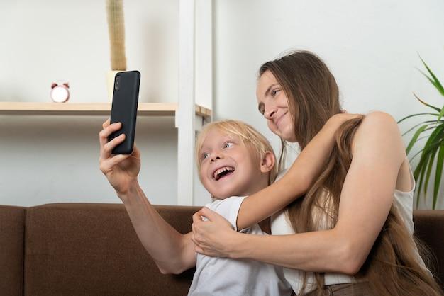 ママと息子はソファで自宅のスマートフォンで抱きしめ、自分撮りをします。
