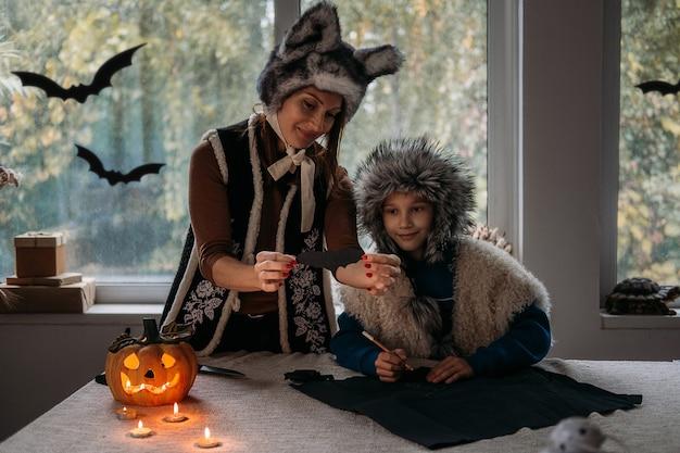 Мама и сын в костюмах на хэллоуин играют вместе и лепят украшения на хэллоуин из бумажных летучих мышей на тыквах