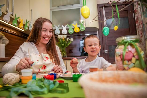 장식 된 부엌에서 집에서 부활절 달걀 그림 과정에서 엄마와 아들