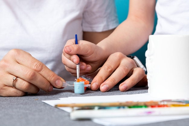 Мама и сын в белых футболках занимаются росписью, крошат кружку на синем фоне. изучение основ рисования в дошкольном возрасте