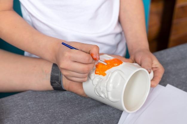 白いtシャツを着たママと息子は絵を描いており、青い背景にマグカップを崩します。就学前の年齢で描画の基本を学ぶ