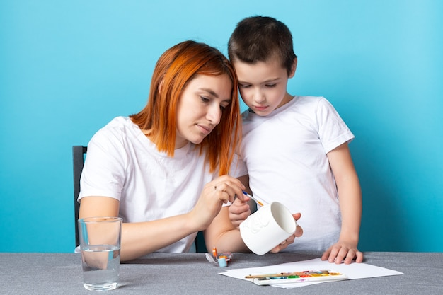흰색 티셔츠를 입은 엄마와 아들이 그림에 종사하고 파란색 배경에 머그잔을 무너 뜨립니다.