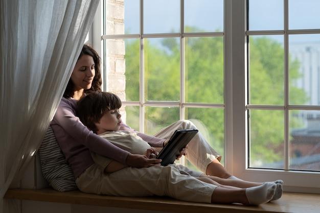 ママと息子の子供は窓辺に座ってタブレット画面を見て母または乳母は家で息子と一緒に時間を過ごす