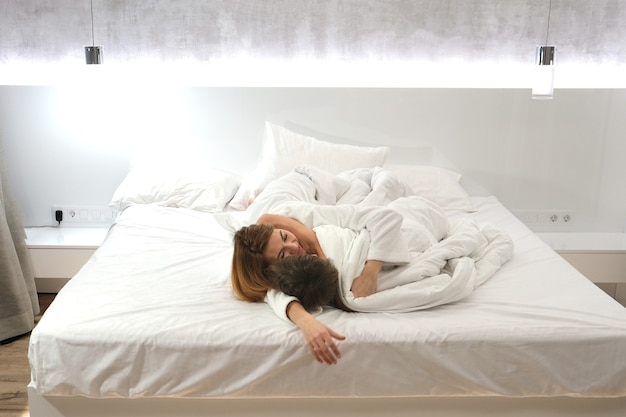 엄마와 아들은 침실의 흰색 침대에 누워 포옹합니다. 어머니.