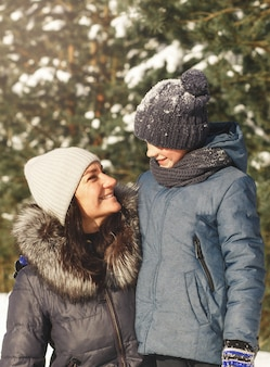 Мама и сын смотрят друг на друга зимой на природе. семейный портрет