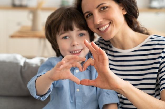 ママと息子が一緒にハートの手振りをする