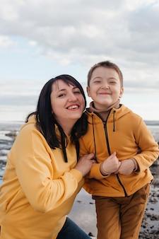 川岸のママと息子。黄色いパーカーを着た息子と一緒の美しい少女は心から微笑む。野外レクリエーション。