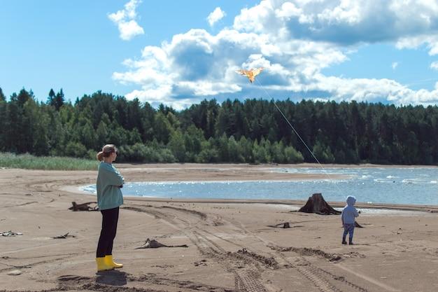 ママと息子は川岸で空飛ぶ凧をします