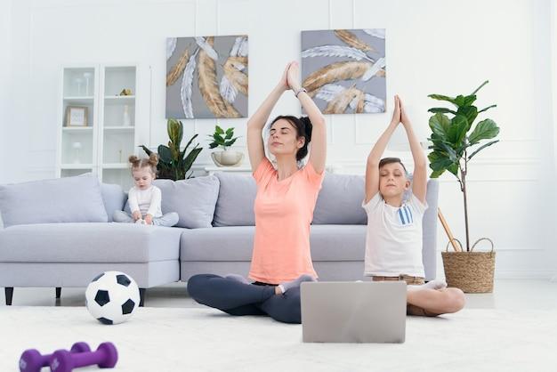 엄마와 아들 집에서 노트북으로 요가 연습. 아침에 운동하는 아이와 어머니입니다. 건강한