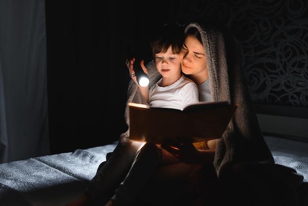 ママと息子が毛布の下で懐中電灯で本を読んで