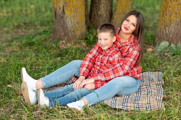 ママと息子、ベッドカバーに寄りかかって、抱擁と笑顔。あらゆる目的のために。