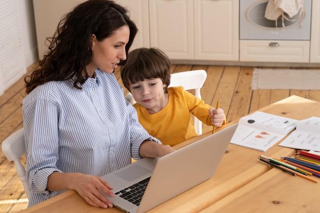 Мама и сын сидят за столом и вместе изучают концепцию домашнего офиса и удаленного семейного образования