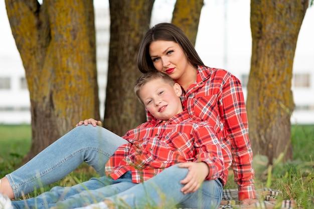 抱き締めてベッドカバーに座っているママと息子。あらゆる目的のために。