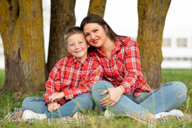 蓮華座でベッドカバーに座って抱き締めるママと息子。あらゆる目的のために。