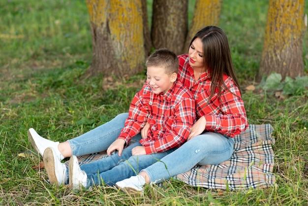 ママと息子は、ベッドカバーに座って、話し、笑顔を見せます。あらゆる目的のために。