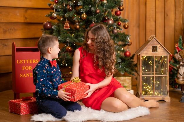 Мама и сын перебирают подарки санты под елкой. семейные праздники, новогодняя сказка