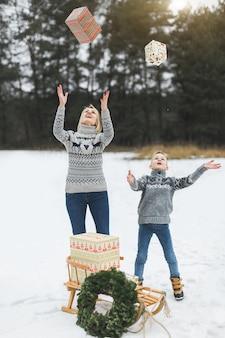 Мама и сын, подбрасывая подарочные коробки, стоя на фоне зимнего леса.
