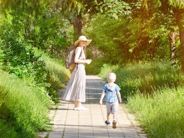 Мама и сын гуляют по дороге в парке.