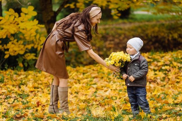 Мама и сын гуляют и веселятся вместе в осеннем парке.