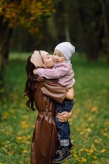 秋の公園で一緒に歩いて楽しんでいるママと息子。