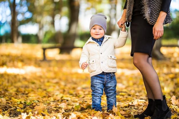 秋の公園を歩いてママと息子