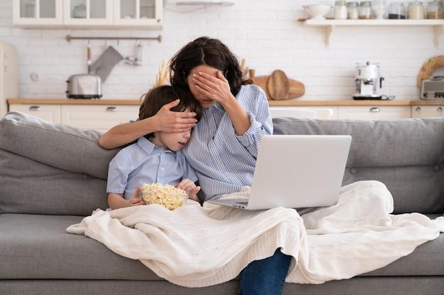 Мама и сын с миской попкорна смотрят страшный фильм, закрывая глаза, сидя на диване у себя дома