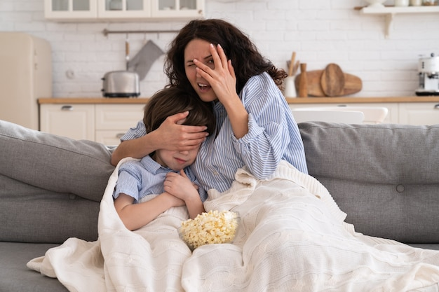 Мама и сын с миской попкорна смотрят страшный фильм