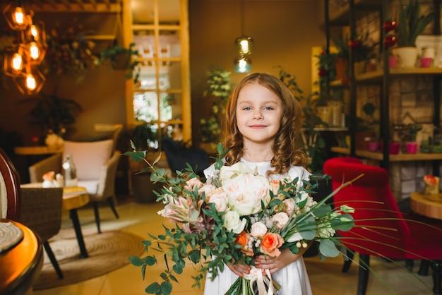 カフェの花を持つママと息子。息子は母親に花をあげます。かわいい家族。国際女性の日、3月8日を祝う