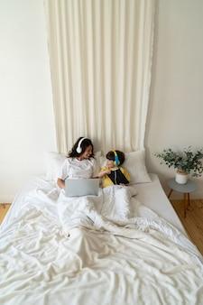 엄마와 아들은 침실에서 노트북 컴퓨터와 디지털 태블릿을 사용하여 침대에 함께 누워 일하고 공부합니다.