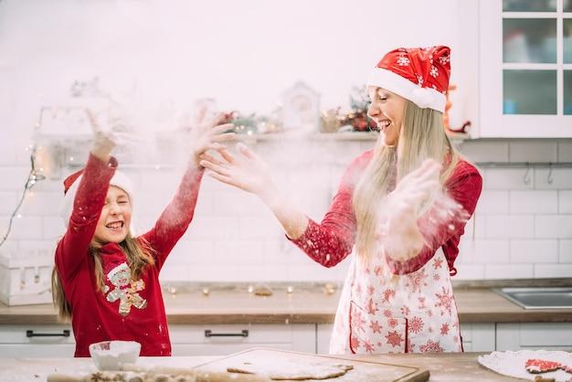 ママと10代の娘は、赤いセーターとサンタの帽子をかぶった小麦粉でキッチンで遊んでいます。