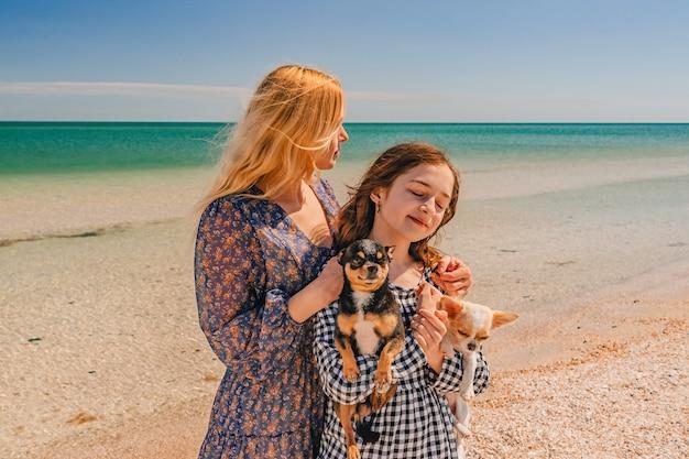 2 匹のチワワ犬と腕を組んでいるお母さんと 10 代の娘。夏の海でのママと娘。
