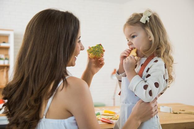 엄마와 유아 딸 크리스마스 진저 쿠키를 굽고. 겨울 휴가를 위해 수제 비스킷을 장식합니다.