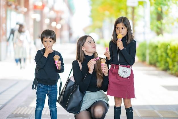 Мама и двое детей едят мороженое с улыбкой на открытом воздухе