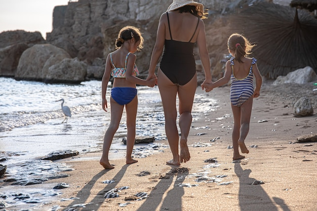 ママと2人の小さな娘が手をつないで水着を着て海岸沿いを歩きます。後ろからv字型。