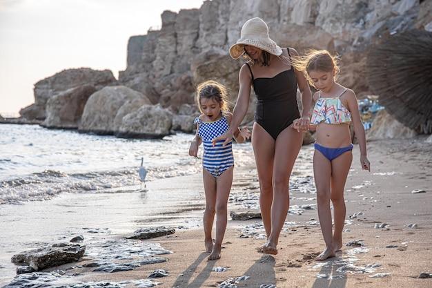 ママと二人の娘が水着を着て海岸沿いを歩き、砂を見ています。海での家族旅行。